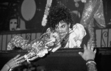 Minneapolis, Minnesota, USA --- Prince crawls toward front of stage and recieves flowers from fan, --- Image by © Mark Downey/Lucid Images/Corbis