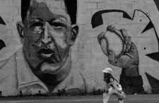 A boy plays baseball near a mural of Venezuela's late president Hugo Chavez, in Caracas, Venezuela September 8, 2016. REUTERS/Henry RomeroCODE: X90174