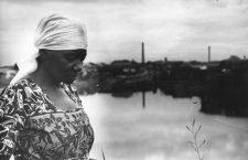 Carolina Maria de Jesus en la rivera del río Tietê con la favela de Canindé al fondo, 1960. Fotografía de Audálio Dantas.