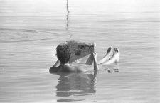 A MAN READING A NEWSPAPER WHILE BATHING IN THE    DEAD SEA.  ðåôù åúééøåú áéí äîìç. áöéìåí, îúøçõ öó áéí äîìç å÷åøà òéúåï.