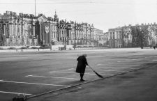 April 30, 1984 - Leningrad, Russia - In early morning a Russian woman sweeps the Palace Square, the central city square of Leningrad (St. Petersburg). In background the façade of the Winter Palace, part of the Hermitage Museum, is decorated for the annual May Day Parade with reviewing stands and portraits of the Central Committee of the Communist Party of the USSR. At right a giant banner with an image of Vladimir Lenin, Communist revolutionary and first leader of the USSR, covers a building façade. (Credit Image: © Arnold Drapkin/ZUMA Wire)
