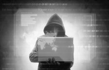 Hacker in black hoodie holding laptop with virtual display server data, chart bar, binary code and world map over dark background