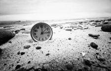 Clock on the beach. Time and business concept. Vintage retro picture.
